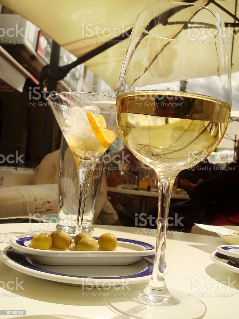 Wine glasses and olives on a sidewalk cafe table. stock photo