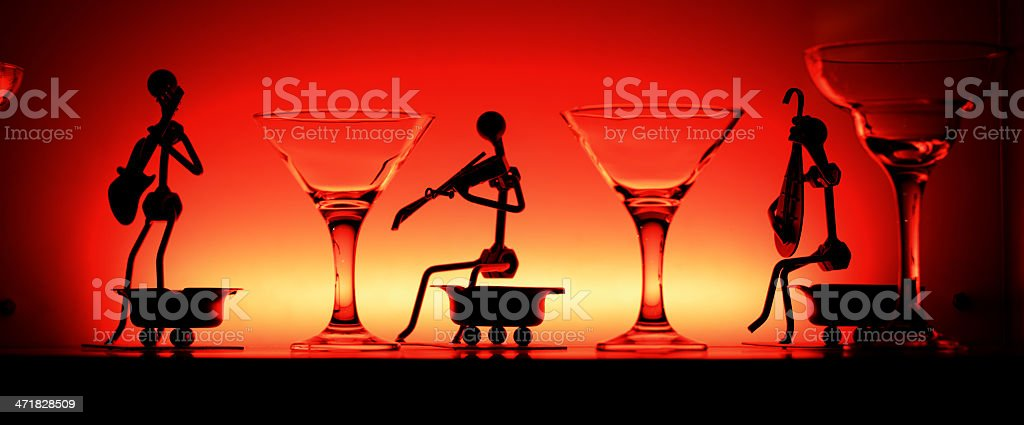 Wine glasses and statuetes in red light royalty-free stock photo
