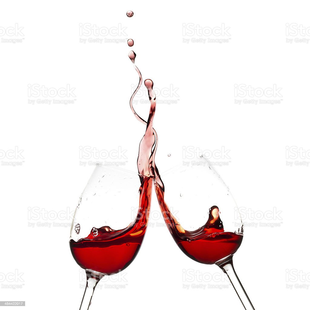 Wine glasses clinking together with red wine stock photo