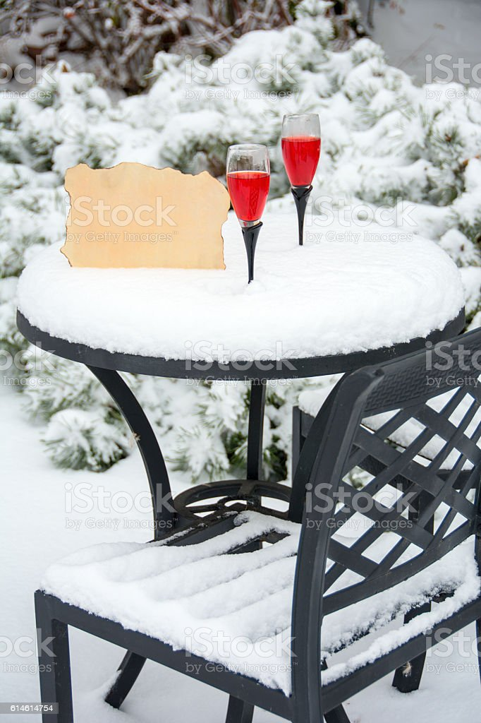 Wine glasses on a snow covered table-  copy  on parchment stock photo
