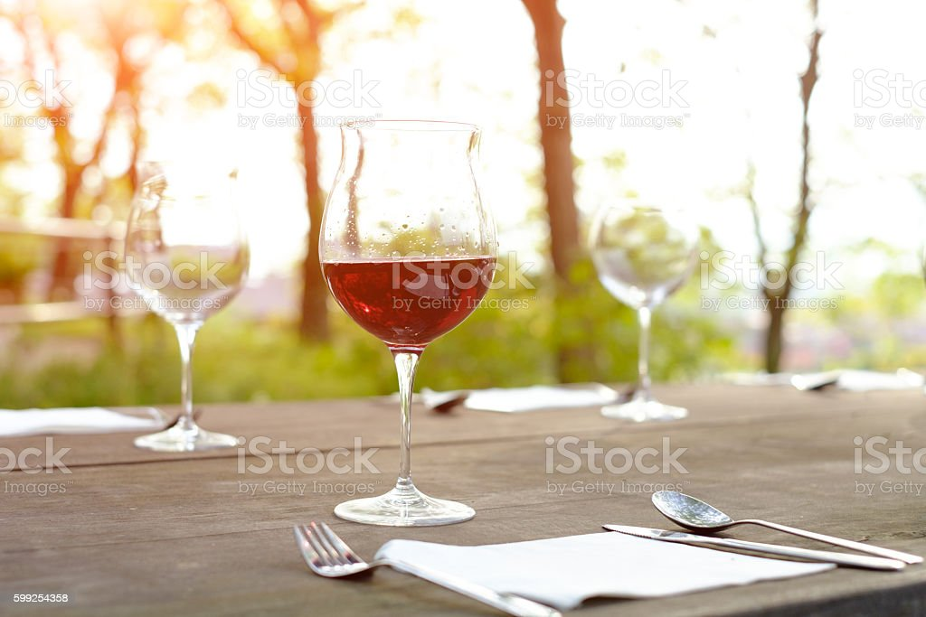 wine glasses on a wooden table in the countryside stock photo