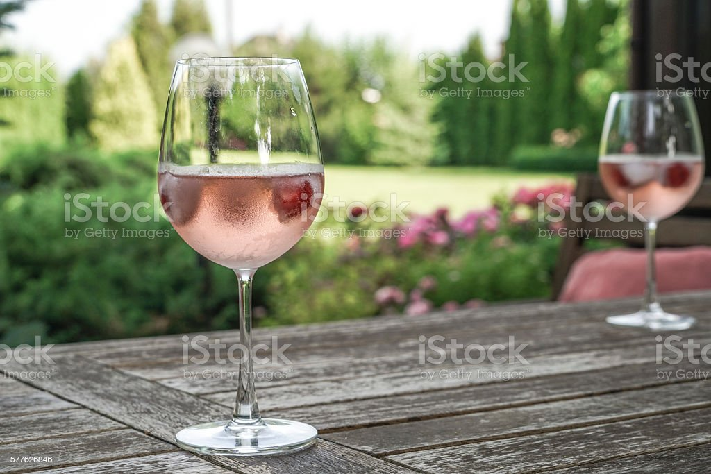 Wine glasses on table at garden stock photo