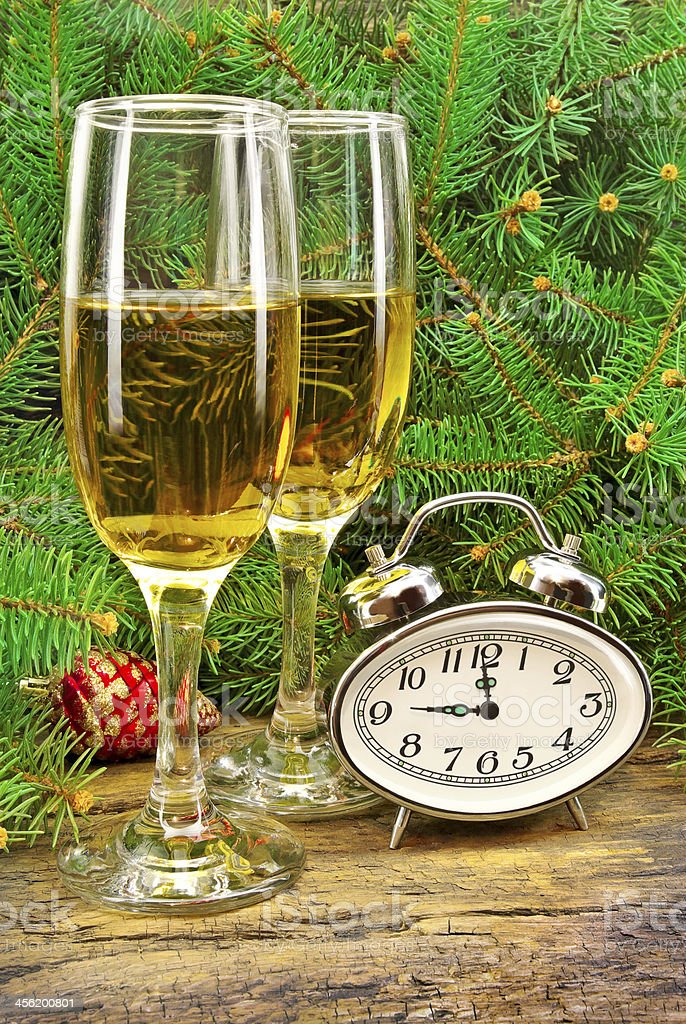 Wine glasses, watches, Christmas toys, near  New Year tree. stock photo