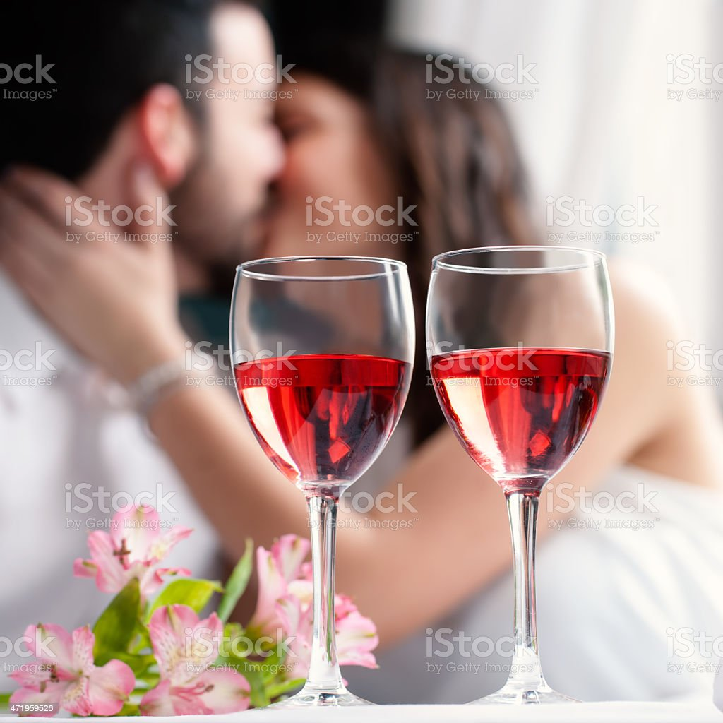 Wine glasses with couple kissing in background. stock photo