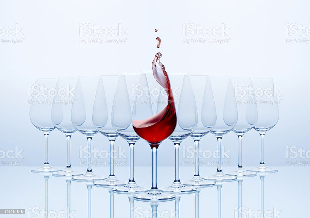Wine glasses with red wine poured into the front glass royalty-free stock photo