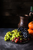 Wine in jug and  of grape on dark background.