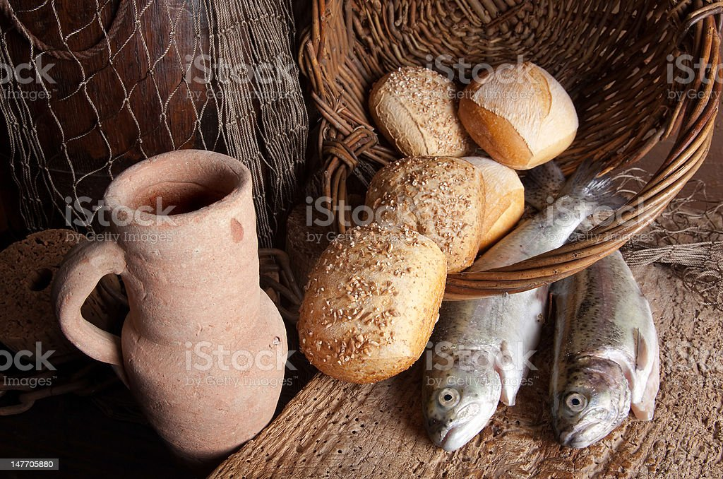 Wine jug with bread and fish stock photo