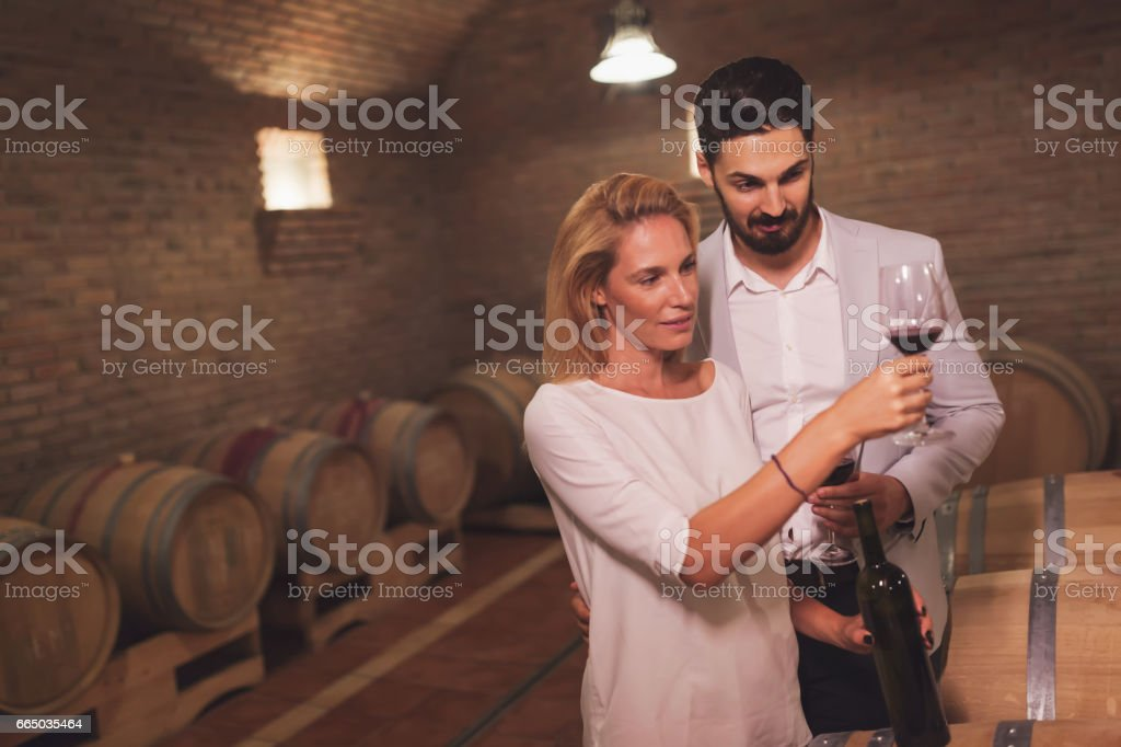 Wine loving couple tasting wines in winery cellar stock photo