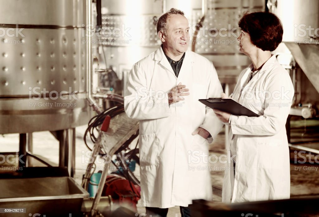 Wine maker shows equipment on winery stock photo