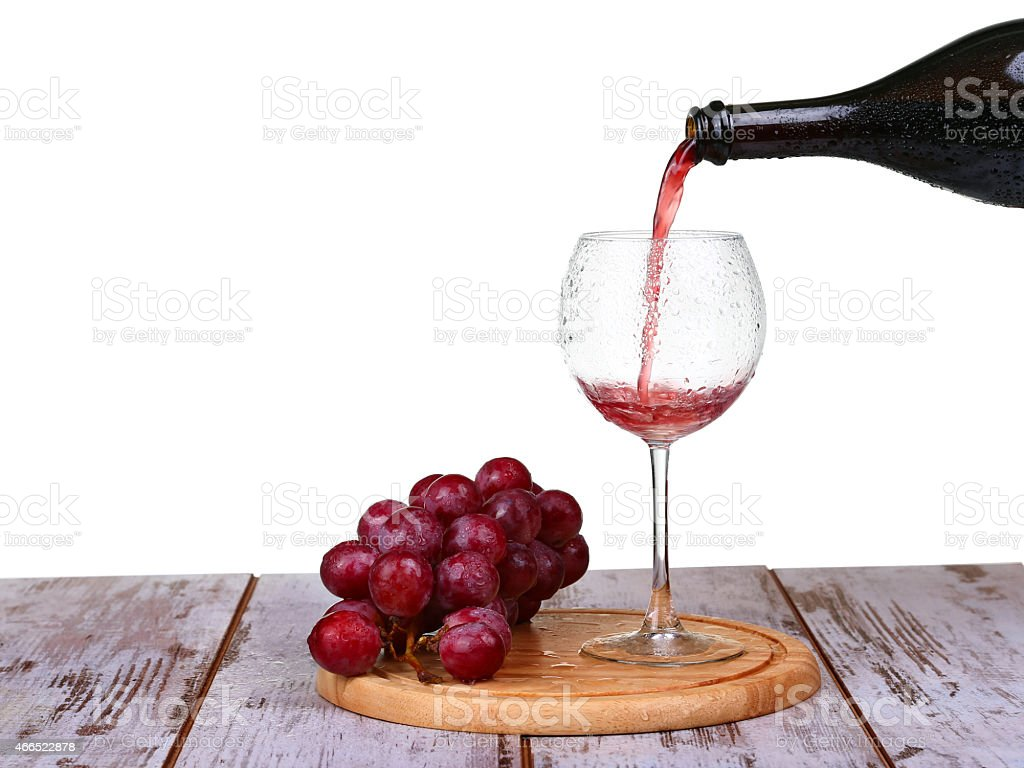 wine pouring into glass with grape and bottles isolated stock photo