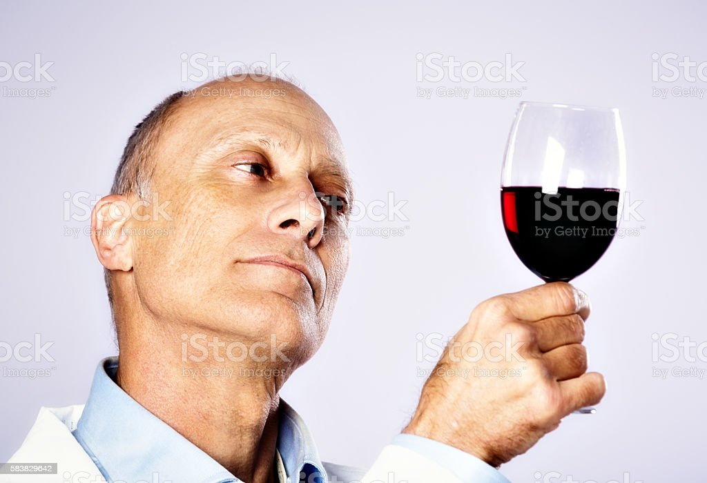 Wine scientist or technician examines glass of red carefully stock photo