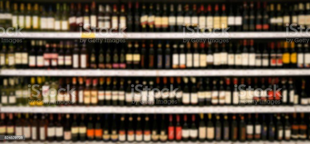 wine shelf in supermarket blurred stock photo