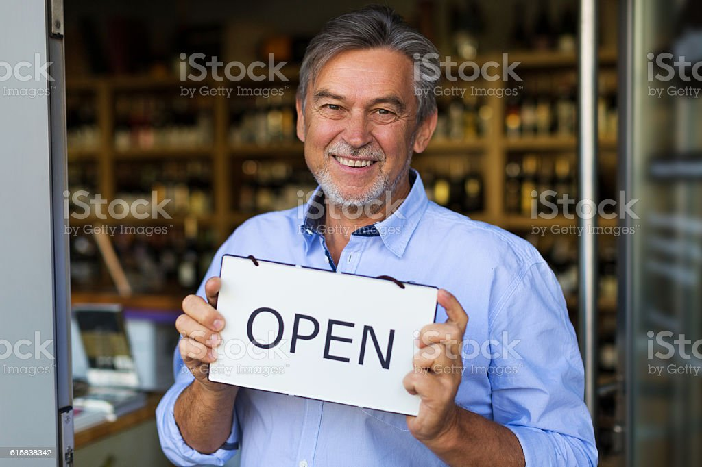 Wine shop owner holding open sign stock photo