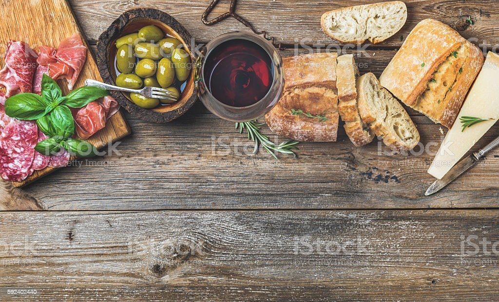 Wine snack set and glass of red over wooden background stock photo