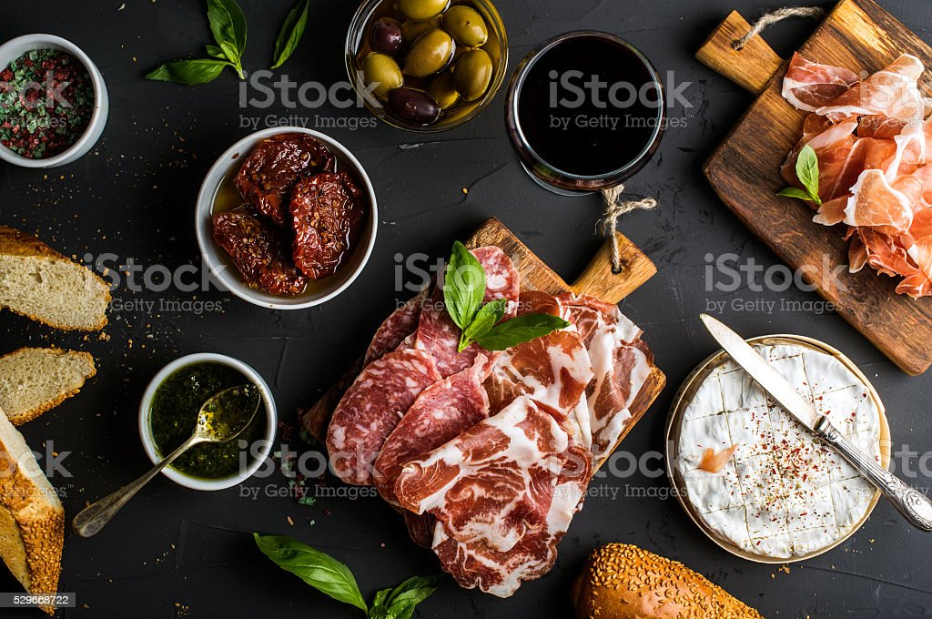 Wine snack set. Glass of red, meat selection, mediterranean olives stock photo
