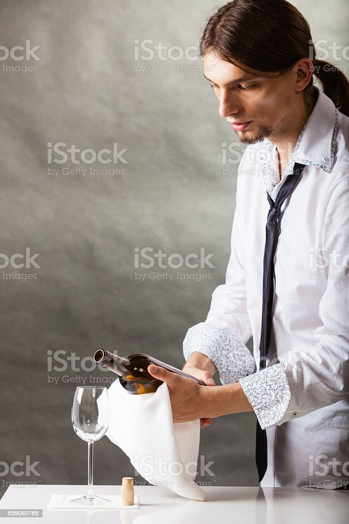 Wine steward fills glass. stock photo