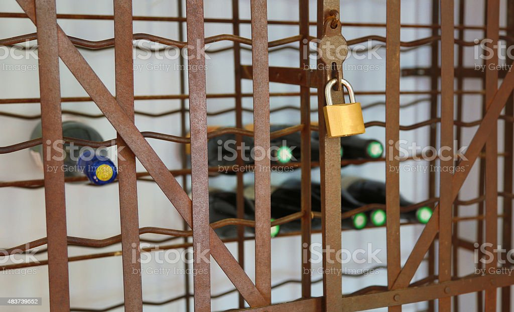 Wine stored in a metal caged with padlock. stock photo