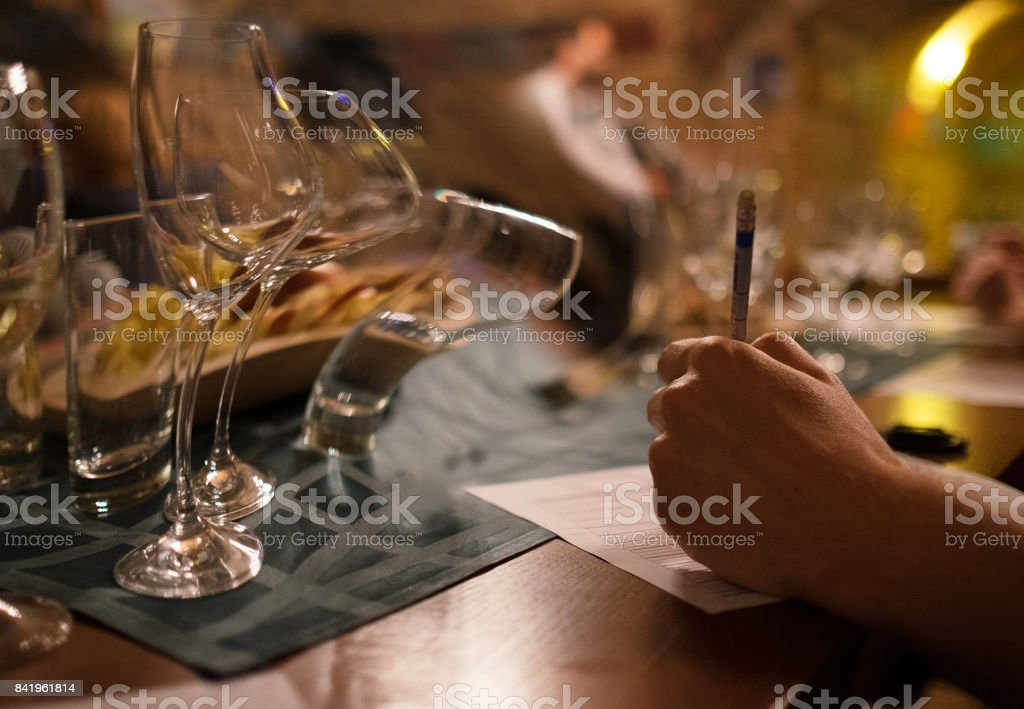 Wine tasting sommelier writes something in note table. stock photo