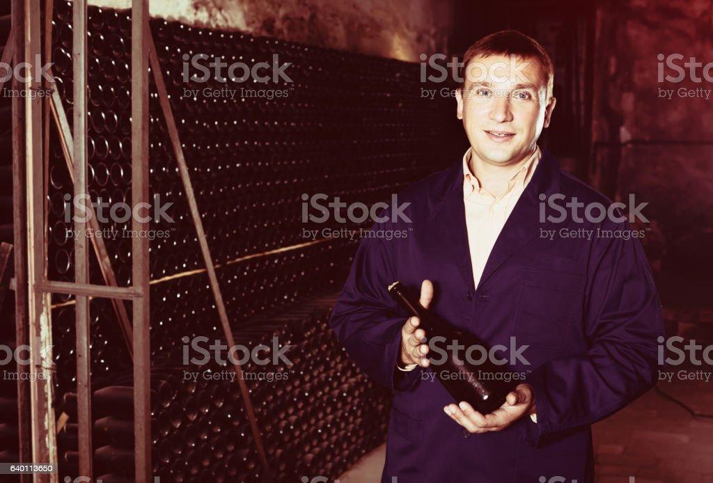 Wine worker in uniform holding bottle near shelves stock photo