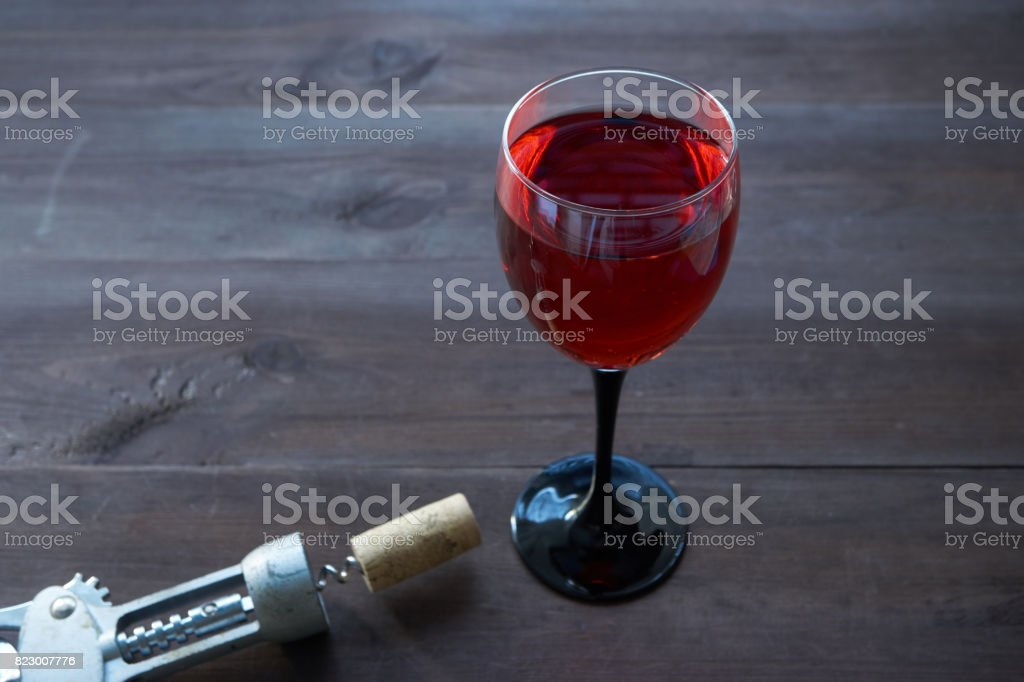 wineglass of red wine on dark brown desk stock photo