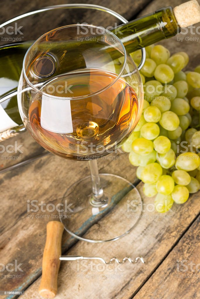 Wineglass with white wine, bottle, corkscrew and cluster of grapes stock photo