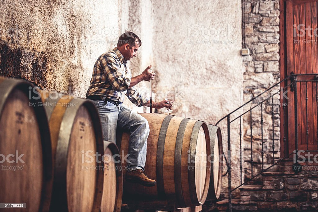 Winemaker Pouring Red Wine into Glass with Pipette stock photo