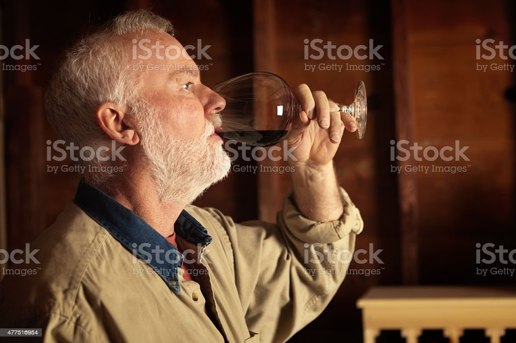 Winemaker Studying and Tasting Wine in Cellar Horizontal stock photo