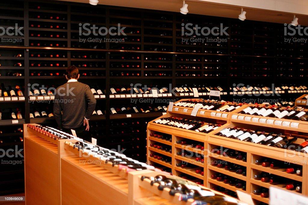 Wine-Store: Man Browsing Racks of Wine Bottles royalty-free stock photo