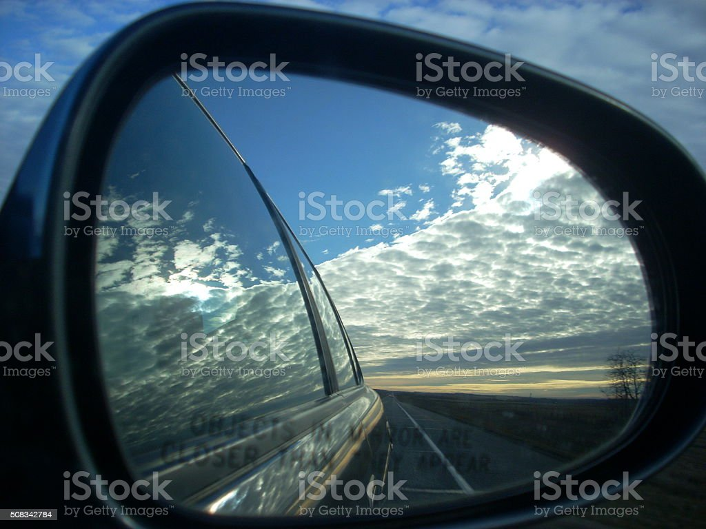 Wing Mirror Reflection of Clouds and Blue Sky stock photo