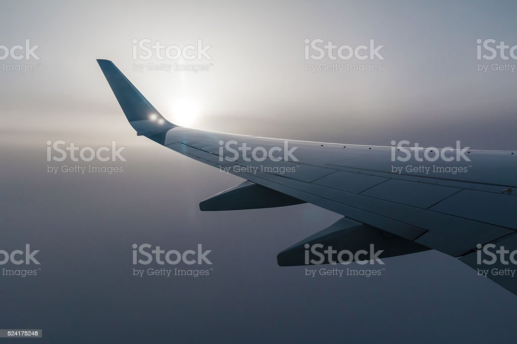 Wing of airplane and sun in fog stock photo