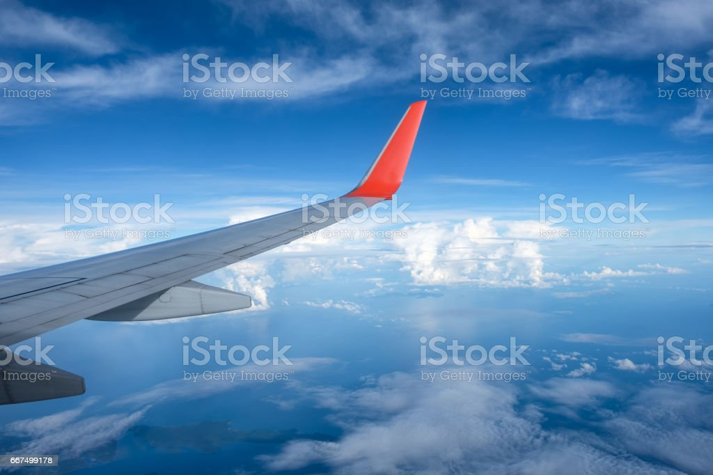 Wing of airplane flying on sky stock photo