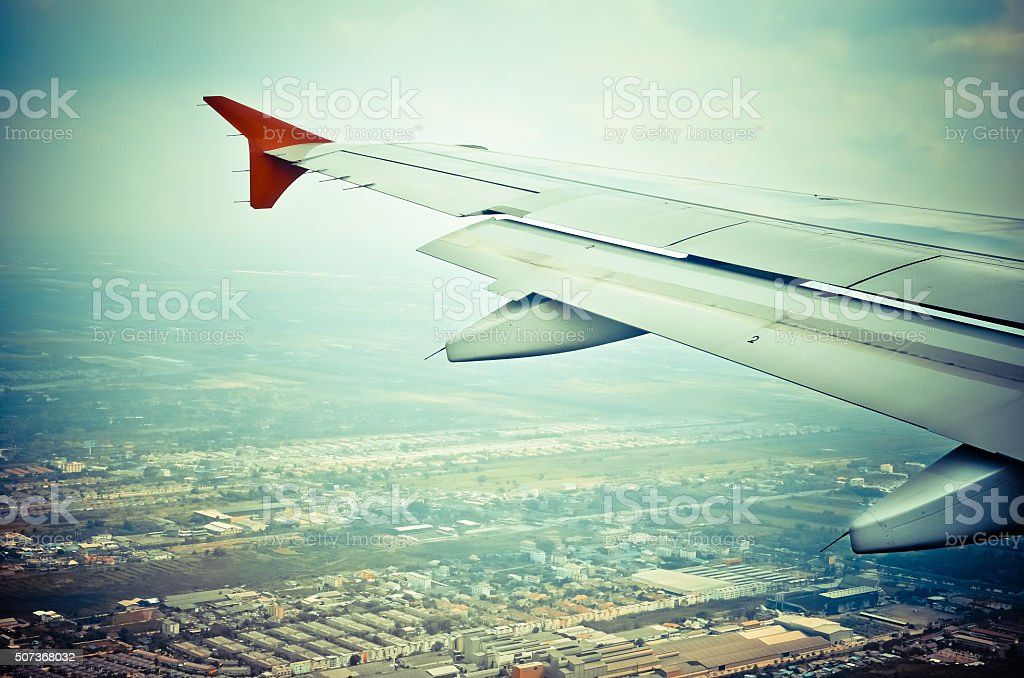 Wing of an airplane preparing to land stock photo
