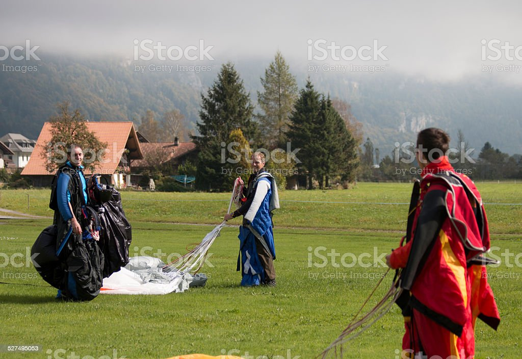 Wing suit fliers gather up parachutes after making jump stock photo