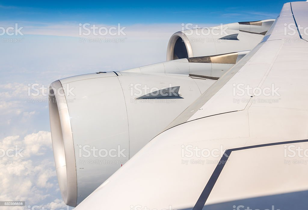 Wing with engines of Airbus A380 flying over clouds stock photo