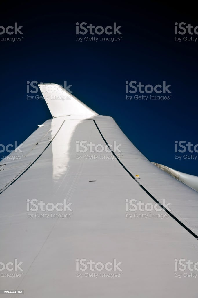 wings of an aircraft in the blue clear sky stock photo