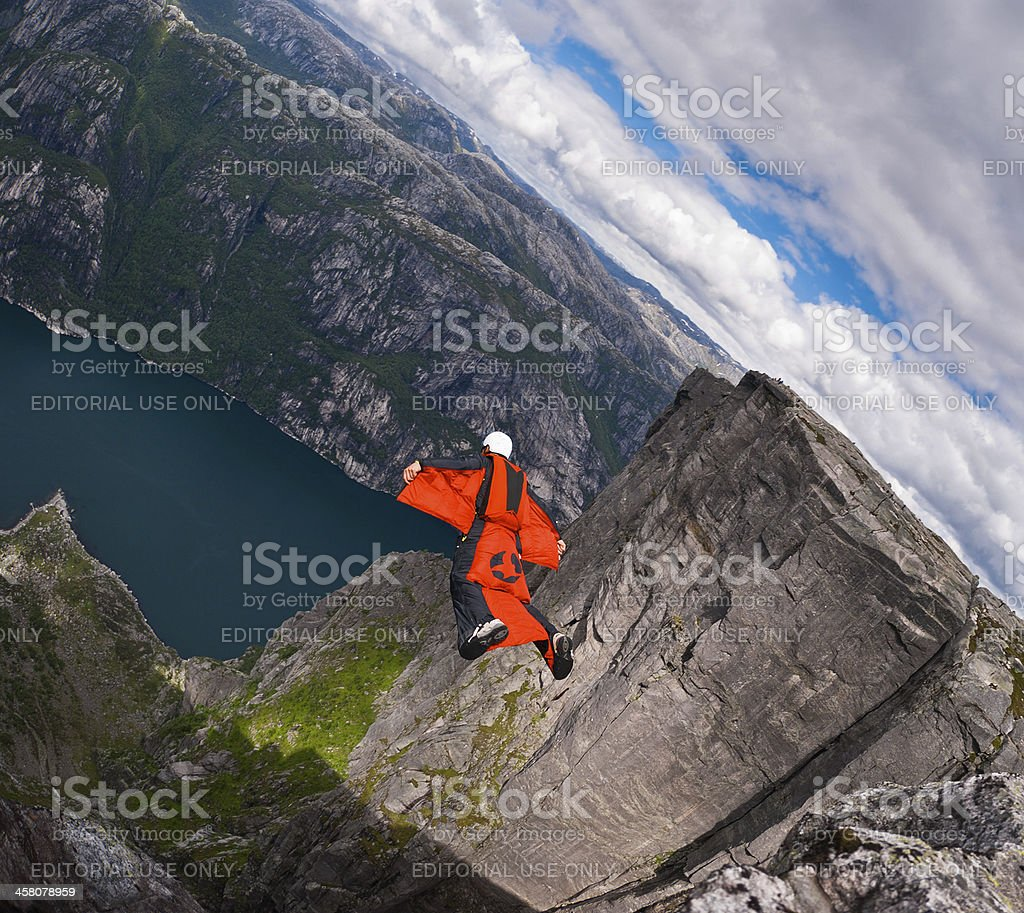 Wingsuit B.A.S.E. jumper jumps off a cliff at Kjerag, Norway. stock photo