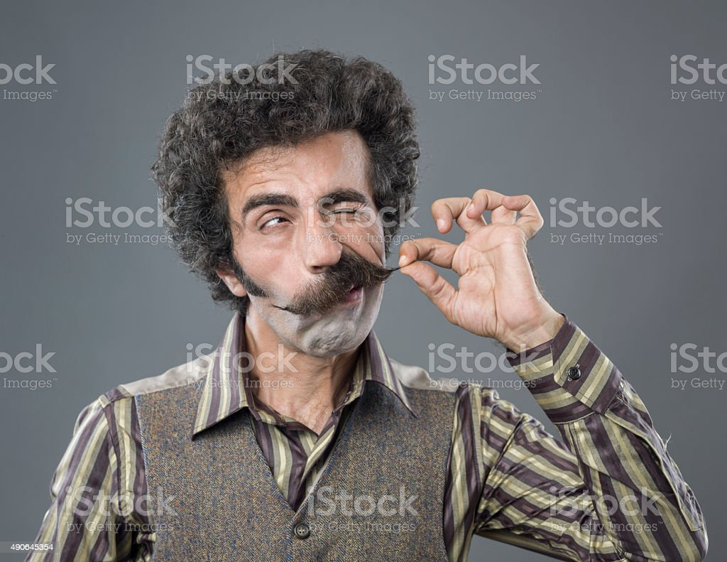 Winking adult man curling up his handle bar mustache stock photo