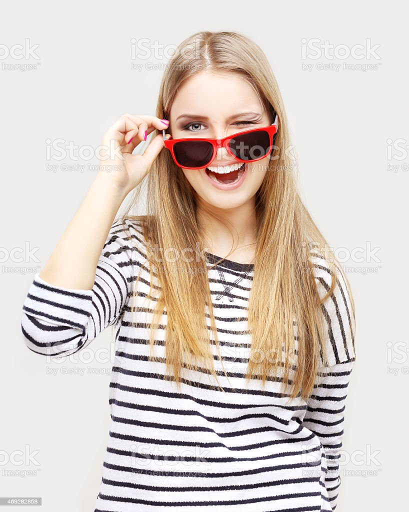 Winking girl  wearing striped top and  red sun glasses stock photo