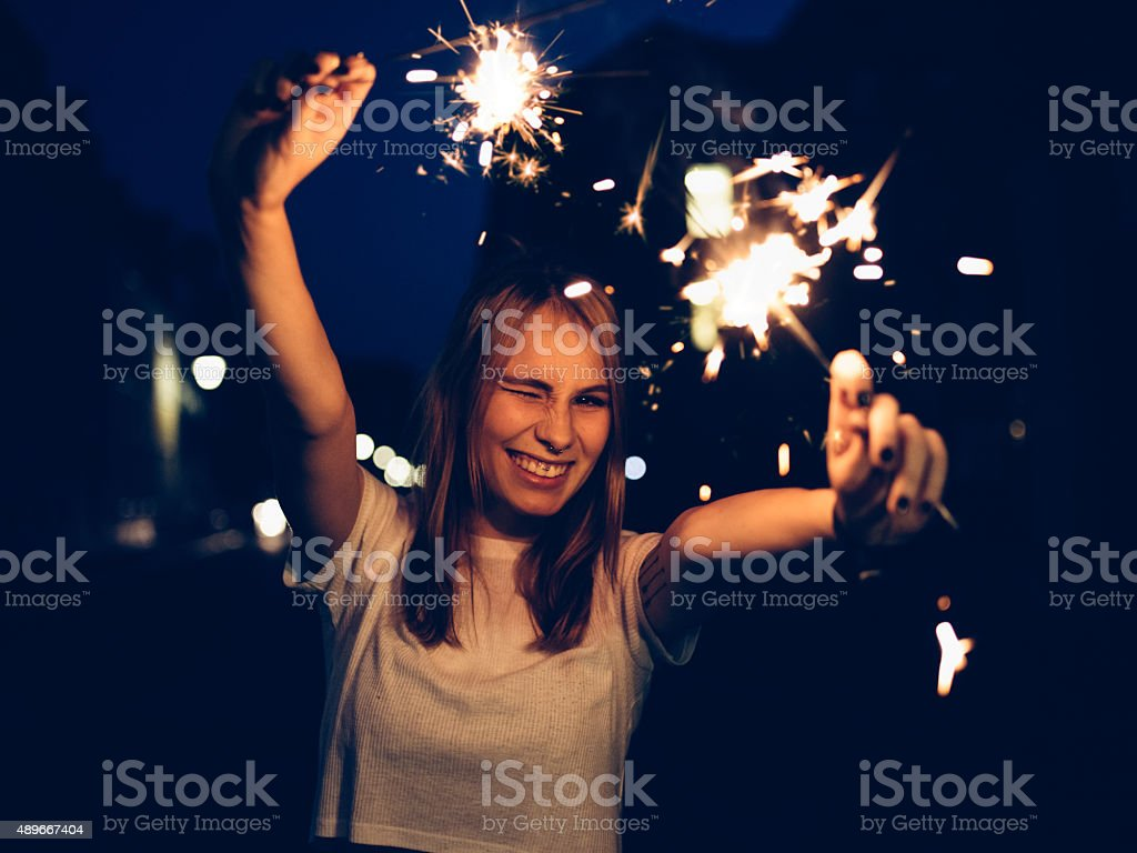Winking teen girl with sparklers on a street at night stock photo