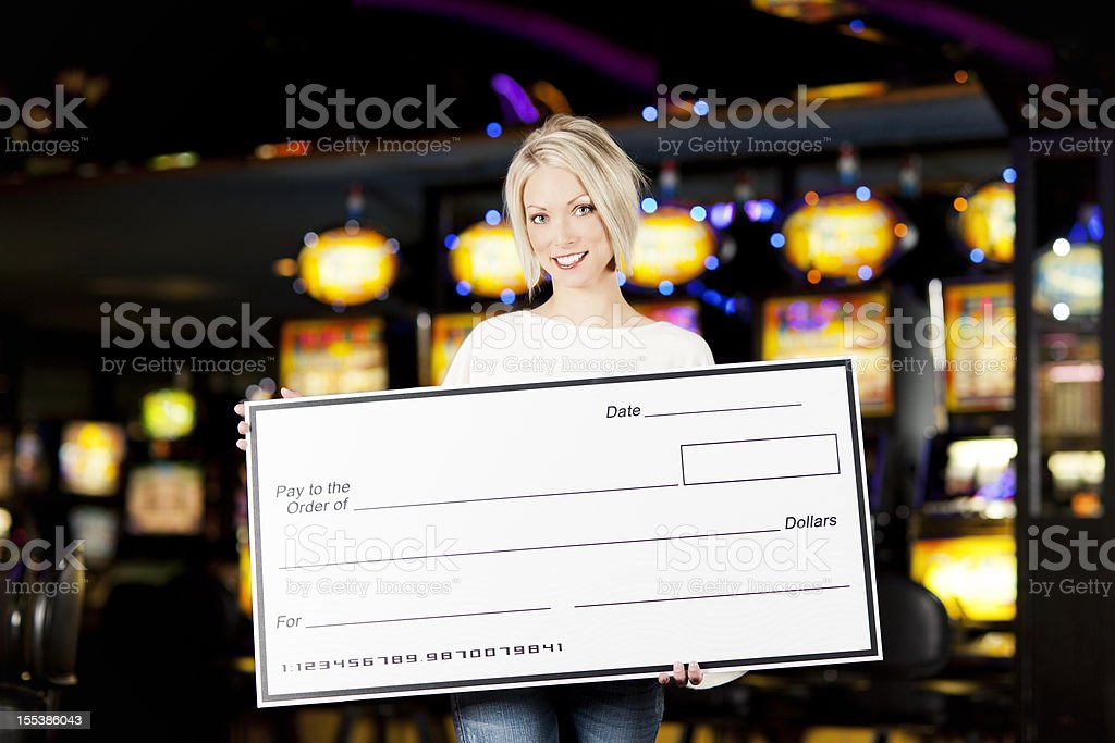 Winner: Happy young woman with blank check in a casino stock photo