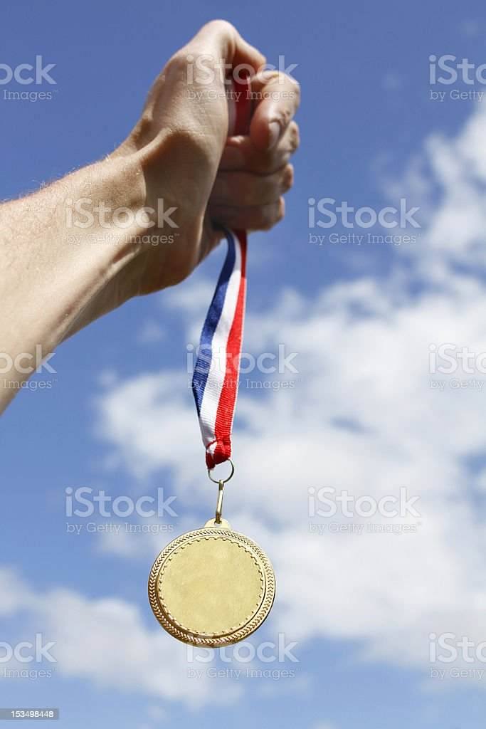 Winning athlete holds Olympic Gold Medal stock photo