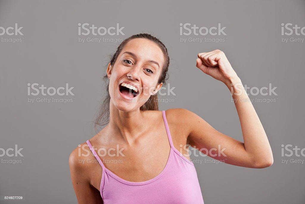 winning girl raising up her arm happily stock photo