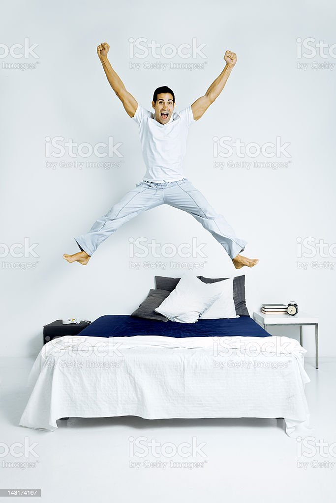 Winning man jumping on bed royalty-free stock photo