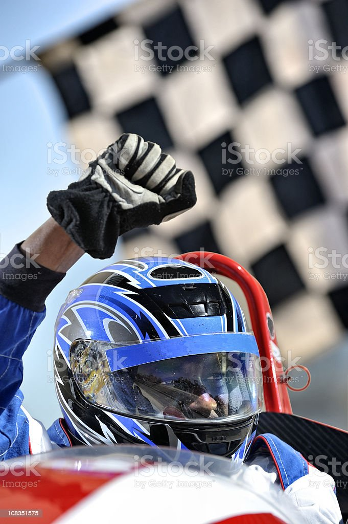 Winning racing driver against flag stock photo