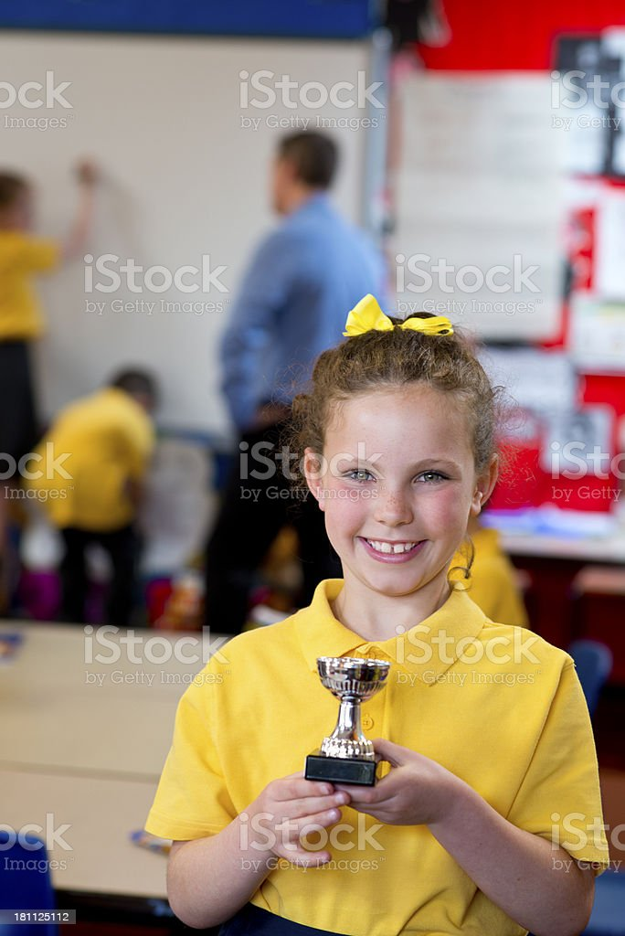 Winning school girl with trophy royalty-free stock photo