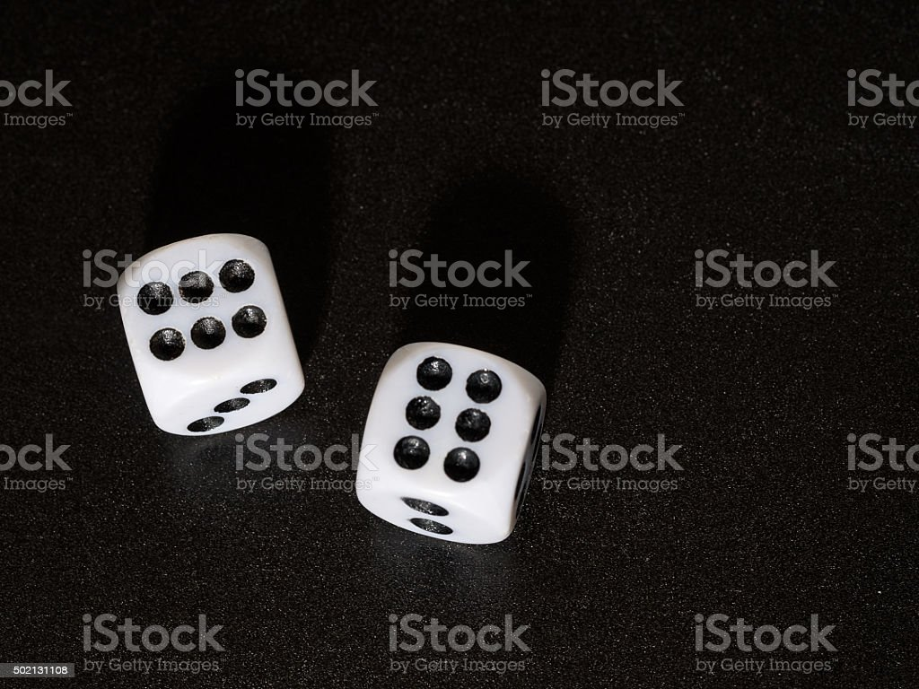 Winning streak. Dice showing number 6 on black textured bacground. stock photo