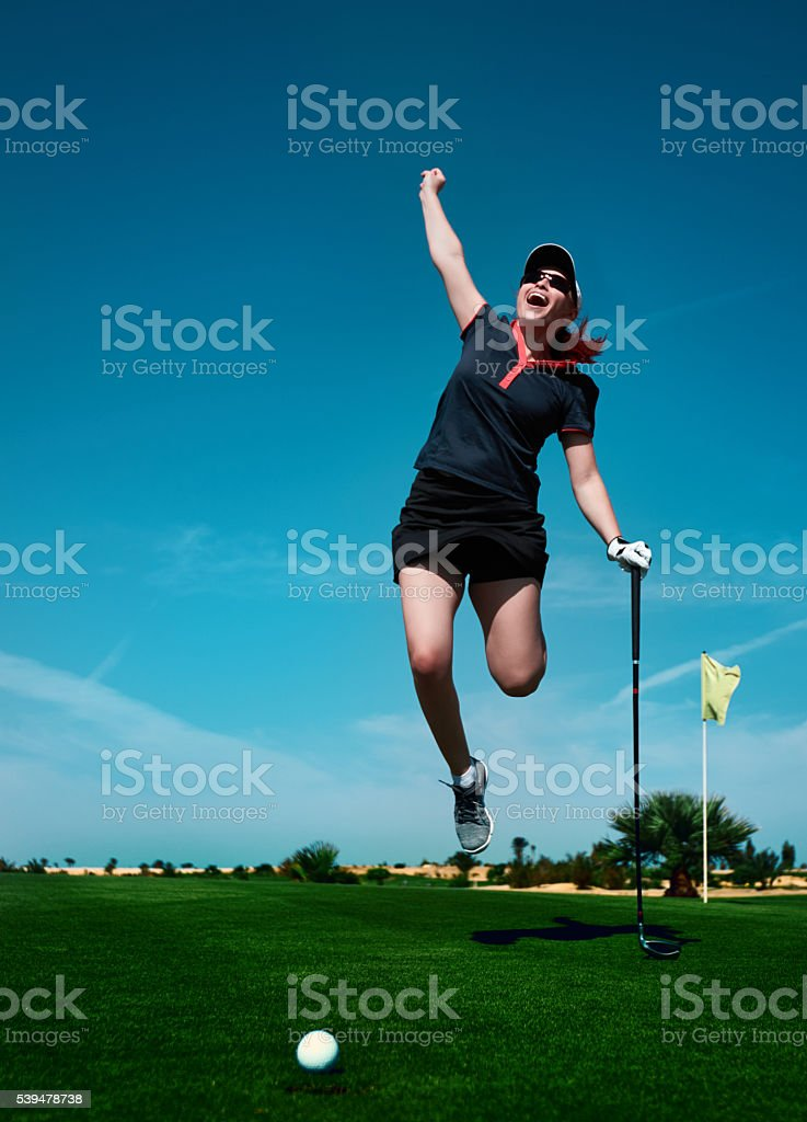 front view of active and happy golf player woman jumping on the golf...