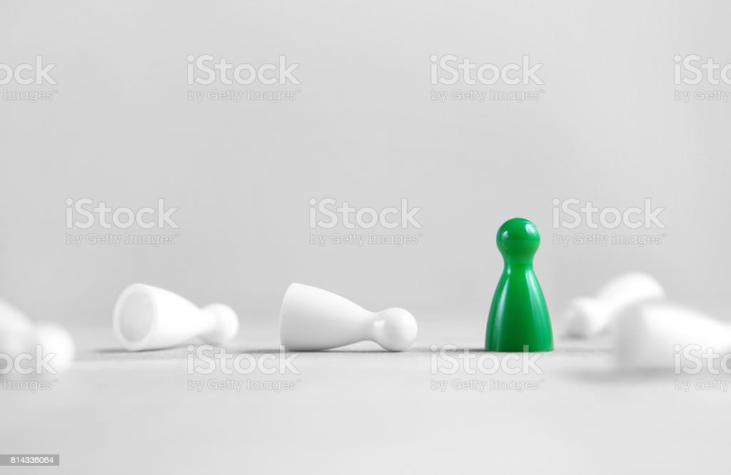 Winning, victory, success and surviving concept. Green board game pawn stand alone, the white rest fallen. Eliminating competitors. One against the others. Last man standing. Against all odds. stock photo