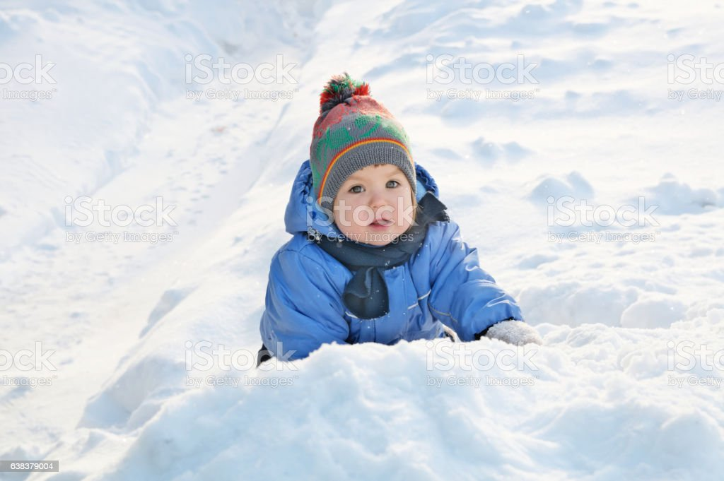 Winter activities concept - little girl outside playing in snow stock photo
