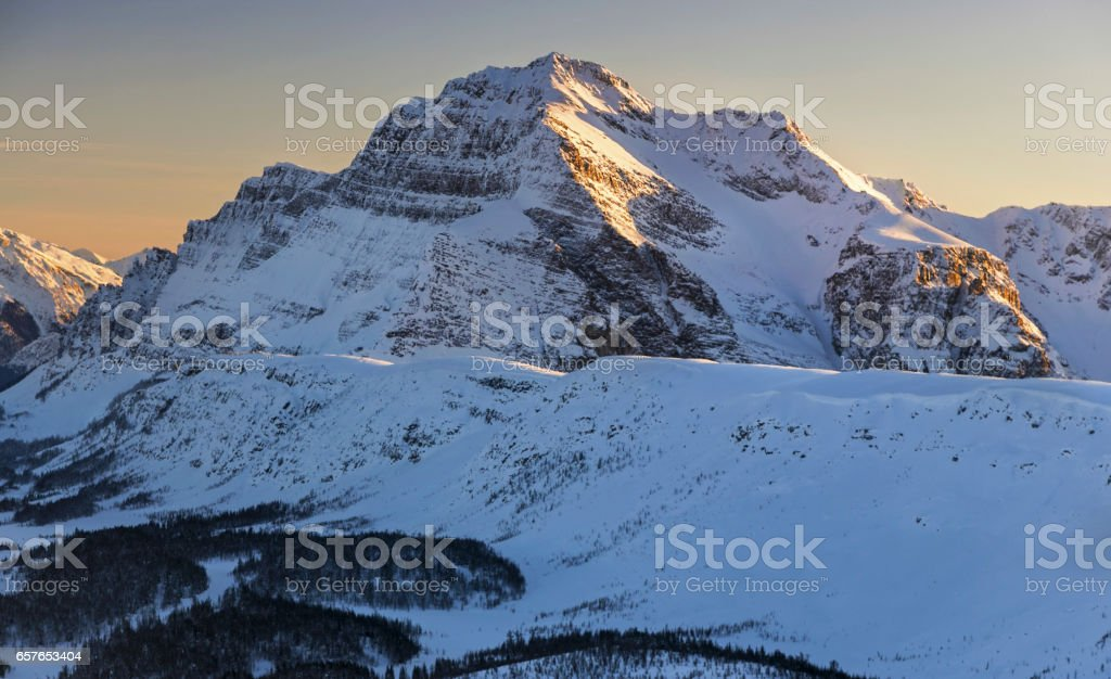 Winter Alpenglow over  Monarch Mountain on Great Divide between Alberta and British Columbia in Canadian Rocky Mountains stock photo